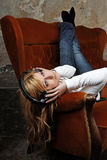 Blondes Mädchen auf Sofa hörend Musik mit Kopfhörern Lizenzfreies Stockfoto
