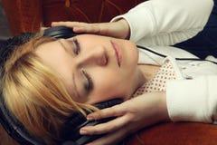 Blondes Mädchen auf Sofa hörend Musik mit Kopfhörern Lizenzfreies Stockbild