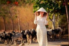 blondes Mädchen auf Vietnamesisch kleiden Notenhut gegen Menge Stockbild