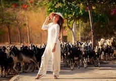 blondes Mädchen auf Vietnamesisch kleiden Notenhut gegen Menge Stockfoto