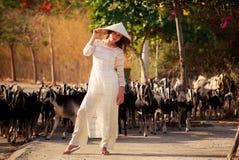 blondes Mädchen auf Vietnamesisch kleiden Notenhut gegen Menge Lizenzfreie Stockfotografie
