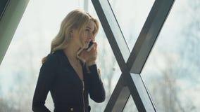 Blondes Mädchen Beautisul im Schwarzen, welches das Fenster bereitsteht und am Telefon spricht lizenzfreie stockfotos