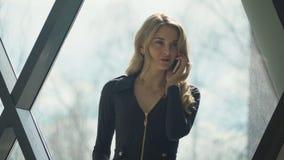 Blondes Mädchen Beautisul im Schwarzen, welches das Fenster bereitsteht und am Telefon spricht stockfoto