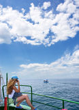 Blondes Mädchen benennt am Telefon, das auf Schreibtisch des Bootes sitzt Stockbilder