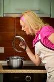 Blondes Mädchen bereitet Nahrung auf Küche zu Stockfotografie