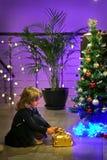 Blondes Mädchen bereitet vor und setzt Geschenke unter den Weihnachtsbaum stockbild