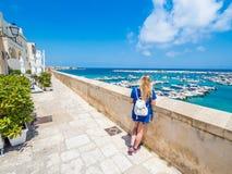 Blondes Mädchen bewundert den Hafen von Otranto, Apulien, Italien lizenzfreies stockfoto