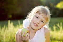 Blondes Mädchen, das Apfel isst Stockbilder