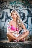 Blondes Mädchen, das Art und Weise nahe Graffitiwand aufwirft Stockbild