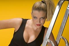 Blondes Mädchen, das auf Aluminiumstrichleiter sich lehnt Lizenzfreie Stockfotografie