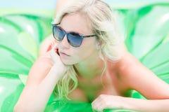 Blondes Mädchen, das auf aufblasbarem ein Sonnenbad nimmt Stockbild