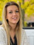 Blondes Mädchen, das auf Bank sitzt Lizenzfreie Stockbilder