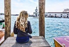 Blondes Mädchen, das auf dem Pier in Venedig sitzt Rückseitige Ansicht lizenzfreie stockfotos