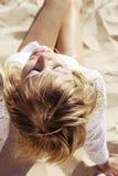 Blondes Mädchen, das auf dem Sand sitzt Lizenzfreies Stockbild