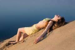 Blondes Mädchen, das auf dem Strand liegt Lizenzfreies Stockbild