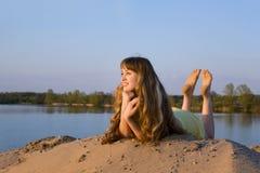 Blondes Mädchen, das auf dem Strand liegt Lizenzfreie Stockfotos