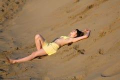 Blondes Mädchen, das auf dem Strand liegt Stockbild