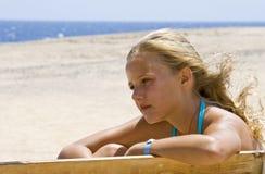 Blondes Mädchen, das auf der Bank sitzt Lizenzfreie Stockbilder