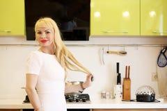 Blondes Mädchen, das auf der Kamera steht in der Küche aufwirft Stockbild