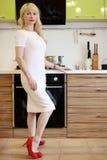 Blondes Mädchen, das auf der Kamera steht in der Küche aufwirft Stockfoto