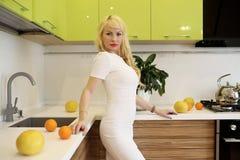 Blondes Mädchen, das auf der Kamera steht in der Küche aufwirft Lizenzfreies Stockfoto