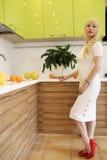 Blondes Mädchen, das auf der Kamera steht in der Küche aufwirft Stockfotos