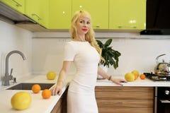 Blondes Mädchen, das auf der Kamera steht in der Küche aufwirft Stockbilder
