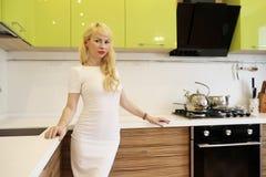Blondes Mädchen, das auf der Kamera steht in der Küche aufwirft Lizenzfreies Stockbild