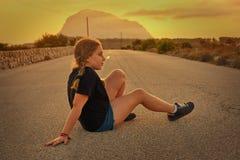 Blondes Mädchen, das auf der Straße mit Montgo sitzt stockbilder