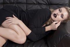 Blondes Mädchen, das auf ein schwarzes Sofa legt Lizenzfreie Stockbilder