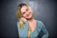 Blondes Mädchen, das auf einem grauen Wandhintergrund lächelt Stockfotografie