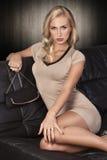 Blondes Mädchen, das auf einem schwarzen Sofa sitzt Stockbild
