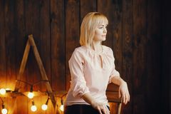 Blondes Mädchen, das auf einem Stuhl sitzt Lizenzfreies Stockbild