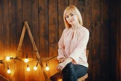 Blondes Mädchen, das auf einem Stuhl sitzt Lizenzfreie Stockbilder