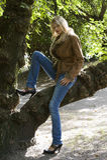 Blondes Mädchen, das auf einem Zweig sitzt Stockfoto