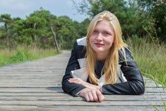 Blondes Mädchen, das auf hölzernem Weg in der Natur liegt Lizenzfreie Stockbilder
