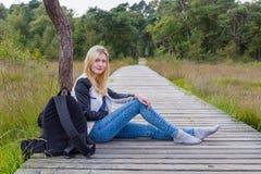 Blondes Mädchen, das auf hölzernem Weg in der Natur sitzt Stockfotos