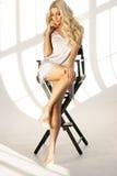 Blondes Mädchen, das auf hohem Direktor ` s Stuhl sitzt Stockbild