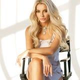 Blondes Mädchen, das auf hohem Direktor ` s Stuhl sitzt Stockfotografie