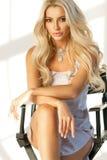 Blondes Mädchen, das auf hohem Direktor ` s Stuhl sitzt Lizenzfreies Stockfoto