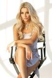 Blondes Mädchen, das auf hohem Direktor ` s Stuhl sitzt Lizenzfreie Stockfotos