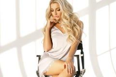 Blondes Mädchen, das auf hohem Direktor ` s Stuhl sitzt Stockbilder
