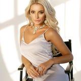Blondes Mädchen, das auf hohem Direktor ` s Stuhl sitzt Stockfotos