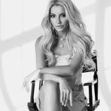 Blondes Mädchen, das auf hohem Direktor ` s Stuhl sitzt Lizenzfreies Stockbild