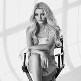 Blondes Mädchen, das auf hohem Direktor ` s Stuhl sitzt Lizenzfreie Stockbilder