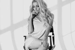 Blondes Mädchen, das auf hohem Direktor ` s Stuhl sitzt Stockfoto