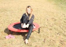 Blondes Mädchen, das auf Socken auf Trampoline nimmt Lizenzfreie Stockfotografie
