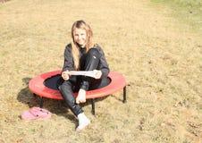 Blondes Mädchen, das auf Socken auf Trampoline nimmt Stockfotografie