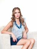 Blondes Mädchen, das auf Stuhl und dem Denken sitzt Lizenzfreies Stockfoto