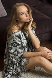 Blondes Mädchen, das auf Teppich sitzt Lizenzfreie Stockbilder